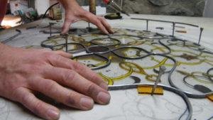 Diego Tolomelli in Iko studio e la tessitura a piombo di una vetrata artistica dipinta a grisaglia e smalti